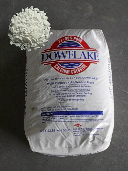 A typical 50lb bag of calcium chloride with inset image showing powder consistency.