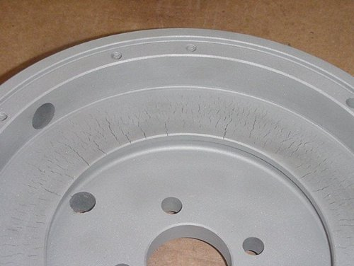 A flywheel with stress cracks due to temperature extremes.