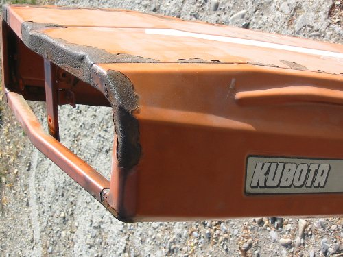 Serious hood rust on the hood of this Kubota is what we are looking to grind down to bare metal with our 60 or 80 grit sandpaper.