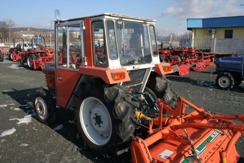 An L1-R Kubota equipped with a cab - note the rear glass panel for viewing ground near the PTO and the rear wiper.