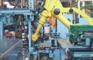 A robot installs pistons on Kubota's automated assembly line.