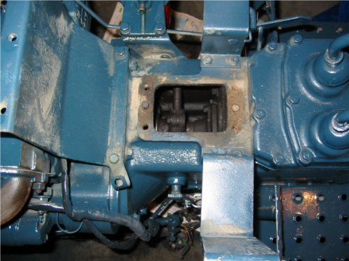 A shot looking down just after the steering box is removed from the top of the clutch housing. The male and female dowels are visible on the left and right as well as the 4 bolt holes where the box was held in place. The clutch shaft is visible in the openening.