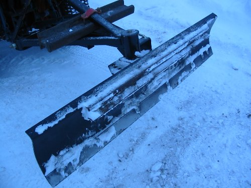 """A typical snow blade that has seen some use. This one, manufactured by Farm King, is in """"back blade"""" position and attached to a Kubota B6200."""